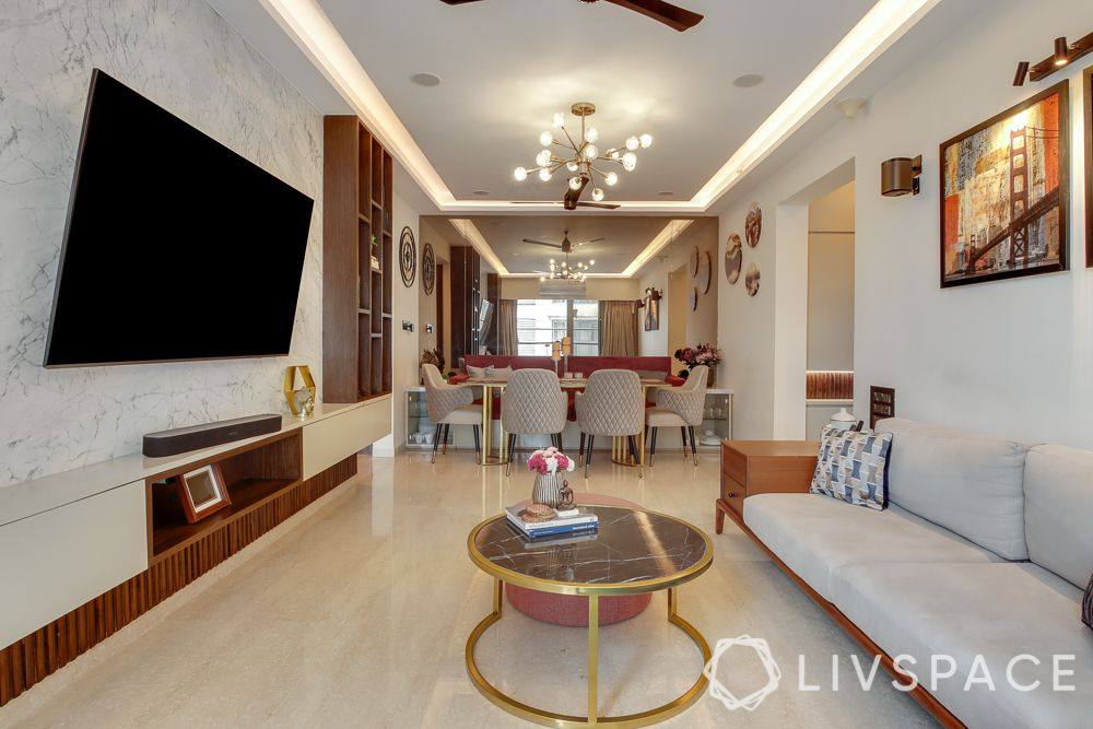 hometour-apartment-in-mumbai-living-room-open-layout-metal-coffee-table-wooden-TV-unit-marble-wall
