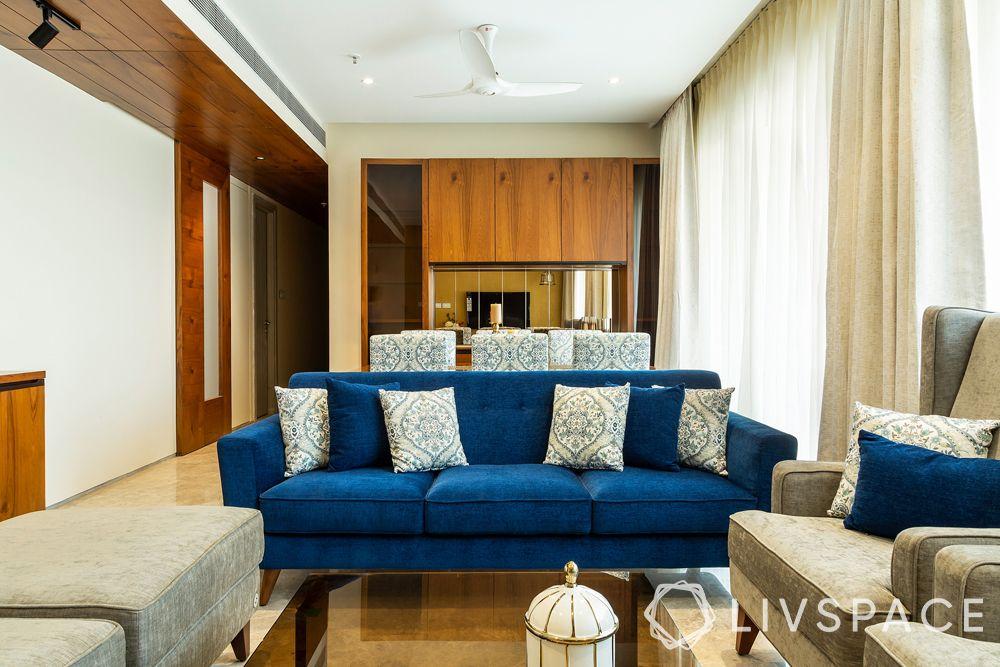 interior-of-3-BHK-flat-living-room-blue-sofa-veneer-panelling