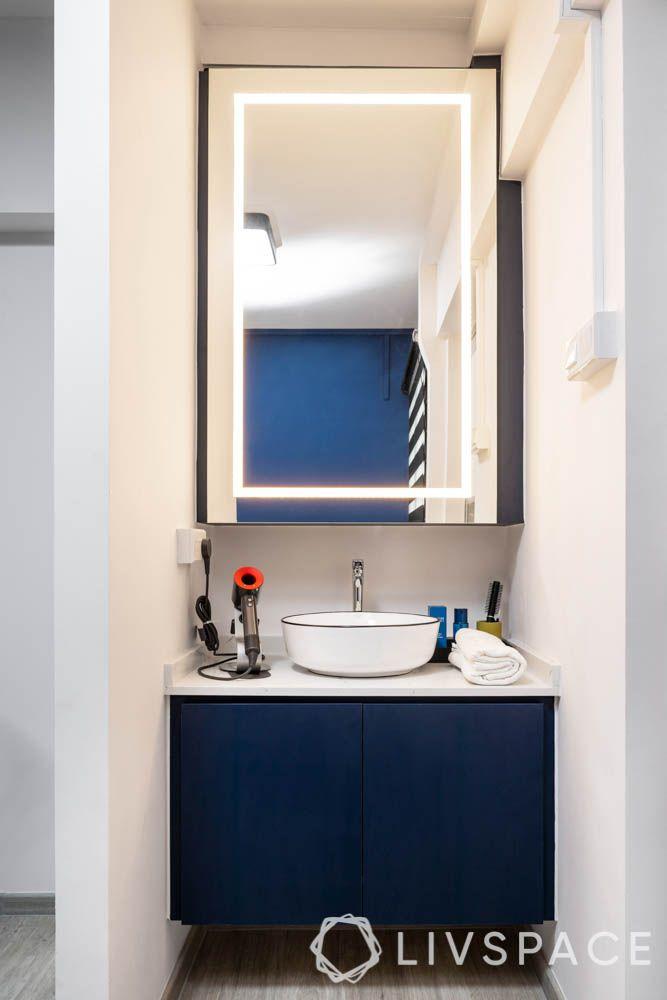 HDB bathroom designs_lighting_dark blue cabinet doors_white counterop_lighted mirror