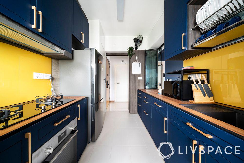 modular kitchen design-blue cabinets-parallel kitchen-glass backsplash