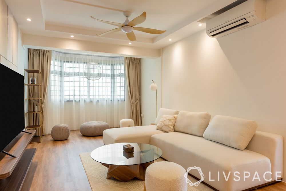 scandinavian-living-room-l-shaped-white-sofa-poufs-wooden-flooring