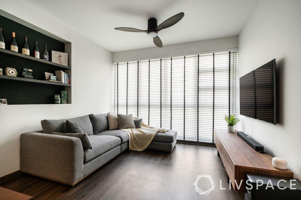 minimal-white-walls-black-shelf-grey-couch-dark-wooden-flooring