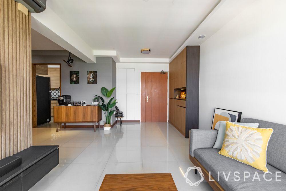 hdb-4-room-resale-renovation-entryway-main-door-grey-couch-wooden-cabinet
