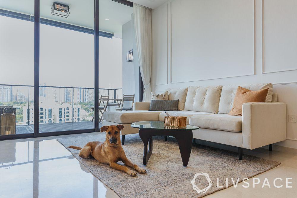 budget-homes-white-panelled-wall-white-sofa-grey-rug-balcony-glass-doors